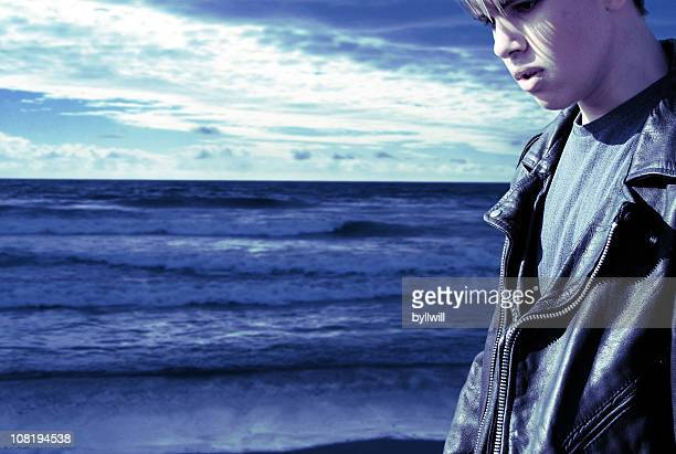 portrait of emo male teenager walking along beach - emo stock photos and pictures