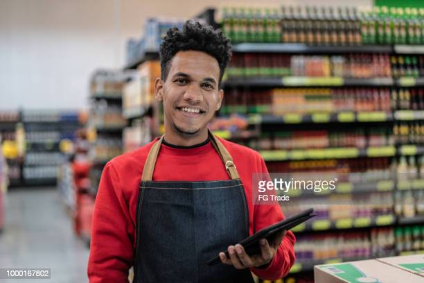portrait of employee checking inventory in a digital tablet at a supermarket - pardo brazilian stock pictures, royalty-free photos & images