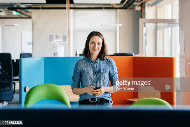 portrait of employee standing in colorful office cubicle - business casual stock pictures, royalty-free photos & images