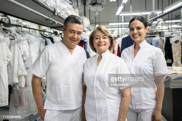 portrait of employees at a laundry service wearing uniform smiling at camera - dry cleaner stock pictures, royalty-free photos & images