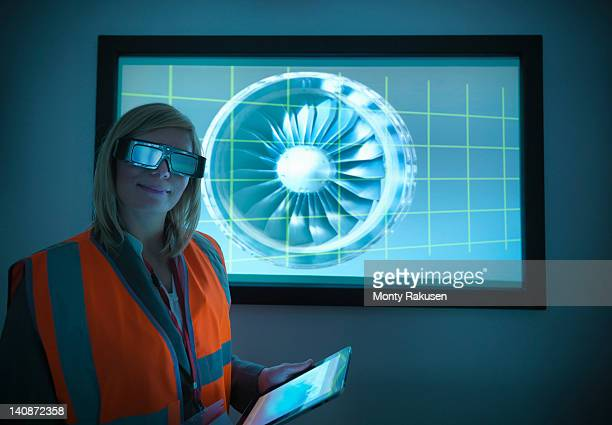 Portrait of engineer holding digital tablet and standing in front of engine part on 3D screen