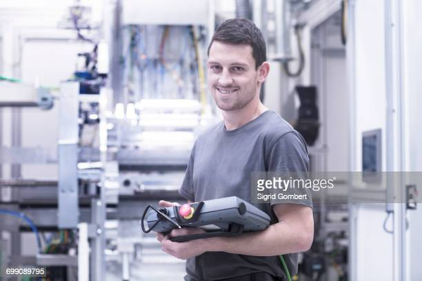 Portrait of engineer holding electronic control equipment in engineering plant