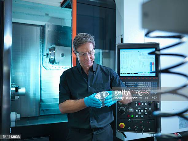 Portrait of engineer holding engineered component at CNC machine in factory