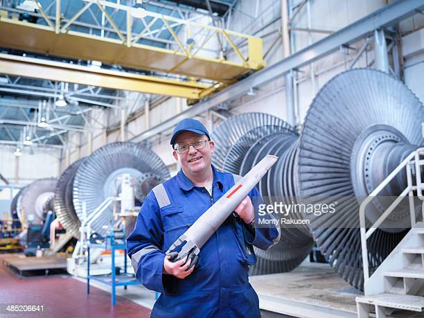 Portrait of engineer holding rotor blade in turbine repair workshop
