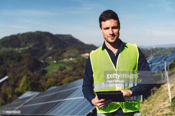 portrait of engineer in neon vest holding a digital tablet working with solar panels - solar mirror stock pictures, royalty-free photos & images