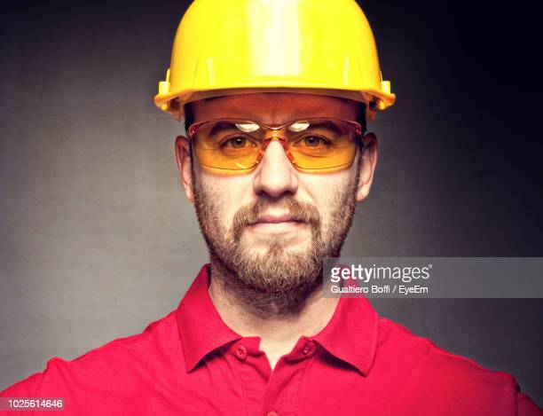 portrait of engineer in protective workwear against wall - protective eyewear stock photos and pictures