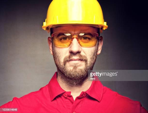 portrait of engineer in protective workwear against wall - schutzbrille stock-fotos und bilder