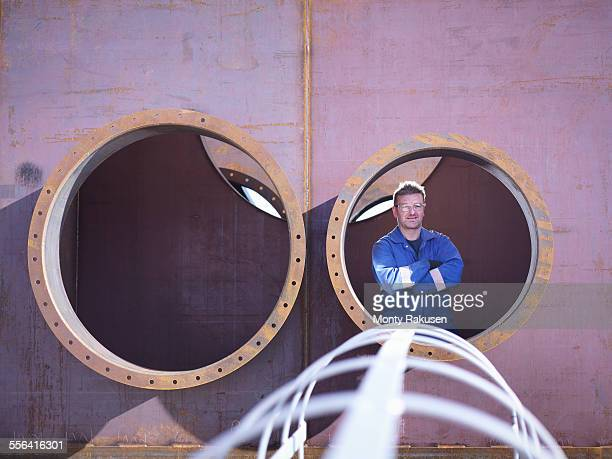 Portrait of engineer inside large steel superstructure in engineering factory
