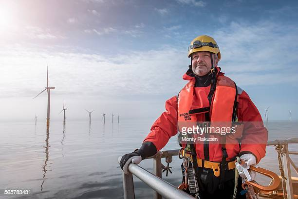 Portrait of engineer on boat at offshore windfarm