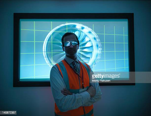 Portrait of engineer standing in front of engine part on 3D screen