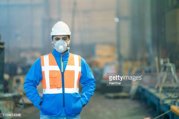 portrait of engineer wearing protective mask in factory - mascherina antipolvere foto e immagini stock