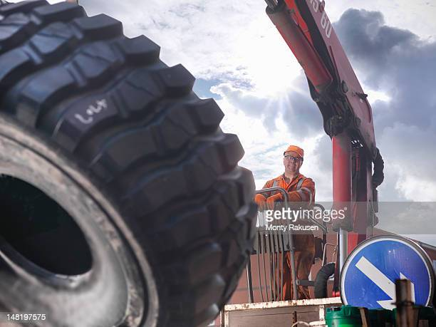 Portrait of engineer with dumper truck tyre under blue sky