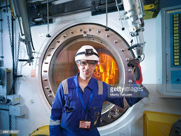 Portrait of engineer with fuel rod handling machine in nuclear power station