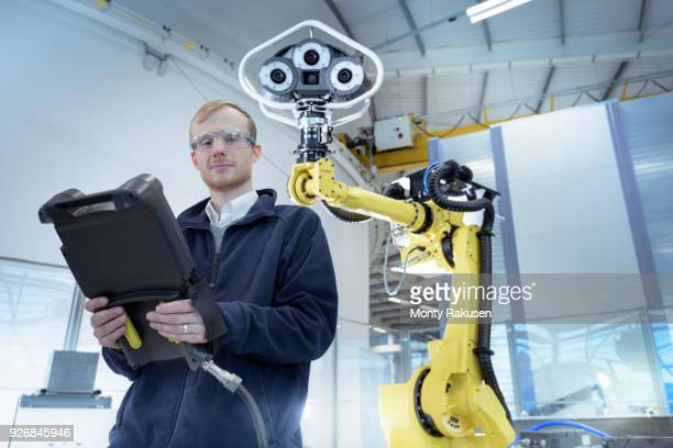 Portrait of engineer with robot in robotics research facility