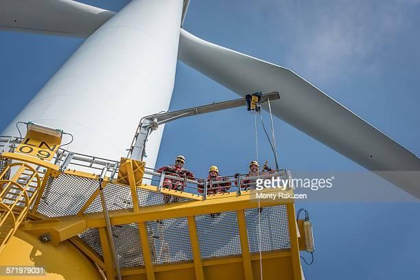Portrait of engineers on wind turbine at offshore windfarm