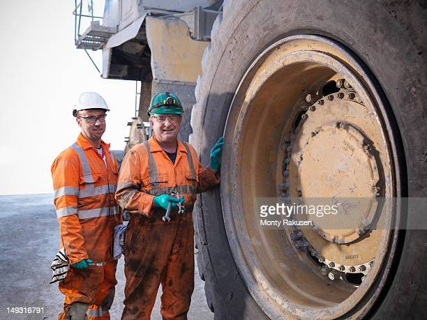 Portrait of engineers working on dumper truck in opencast coalmine