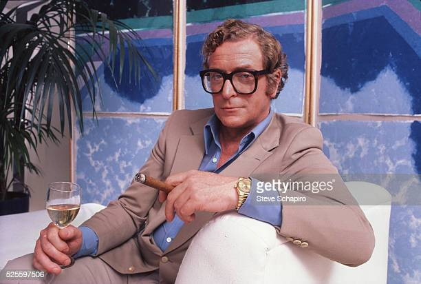 Portrait of English actor Michael Caine, with a wine glass and cigar his hands, poses on a white couch, Los Angeles, California, 1982. Behind him is...