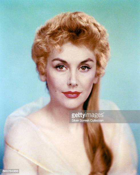 Portrait of English actress and comedienne Kay Kendall as she poses against a blue background late 1940s