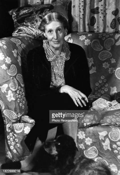Portrait of English author Virginia Woolf as she sits cross-legged on a couch, with her Cocker Spaniel, Pinka, at her feet, London, England, 1939.