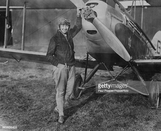Portrait of English aviator Amy Johnson standing next to her plane at an airfield in London January 10th 1930