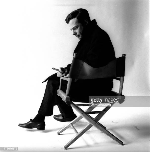 Portrait of English impresario and band manager Brian Epstein holds a cigar as he sits in director's chair, his back to the camera, against a white...