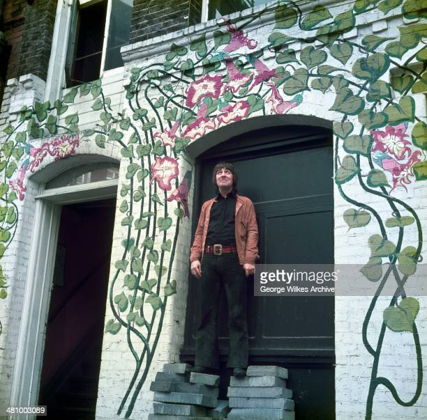 Portrait of English musician Keith Moon of the band the Who as he stands on a pile of bricks under an archway painted with vines and flowers London...
