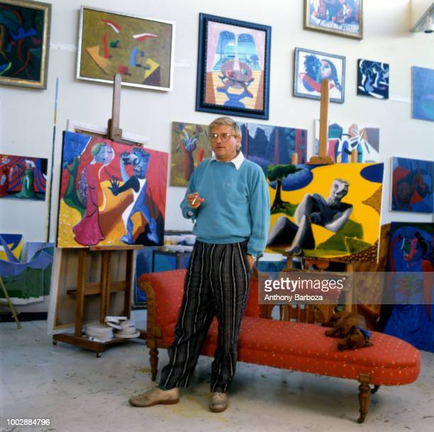 Portrait of English painter David Hockney dressed in a light blue sweatshirt and tan trousers as he stands in front of a chaise longue in his home...