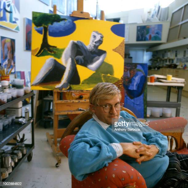 Portrait of English painter David Hockney dressed in a light blue sweatshirt and tan trousers as he sits on a chaise longue in his home Los Angeles...