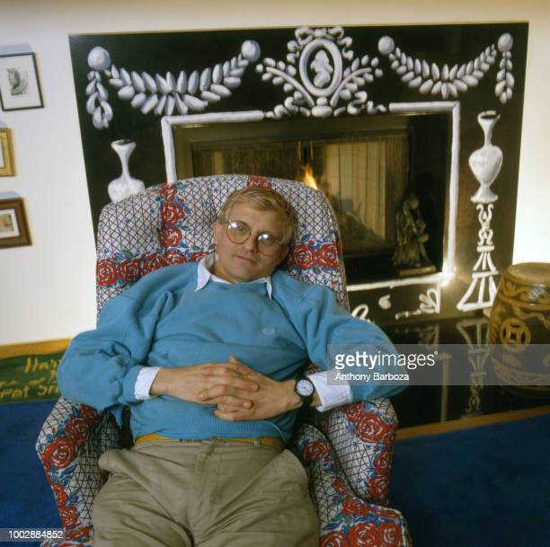 Portrait of English painter David Hockney dressed in a light blue sweatshirt and tan trousers as he sits in an armchair in his home Los Angeles...