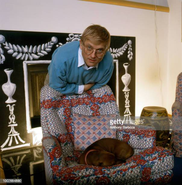 Portrait of English painter David Hockney dressed in a light blue sweatshirt and tan trousers as he leans on the back of an armchair in his home Los...