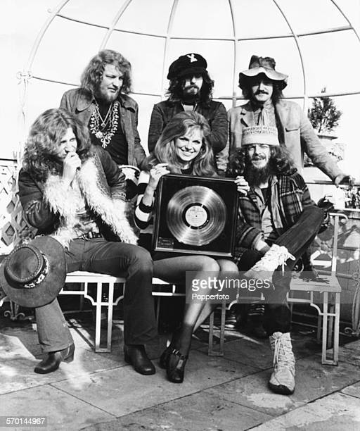 Portrait of English rock band Jethro Tull Martin Barre Jeffrey Hammond Clive Bunker and John Evan and Ian Anderson with actress Julie Ege holding the...