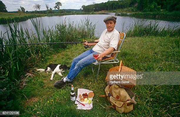 Portrait of English singer and musician, Roger Daltrey relaxing at the water's edge at the trout farm he developed, in the summer of 1989, near...