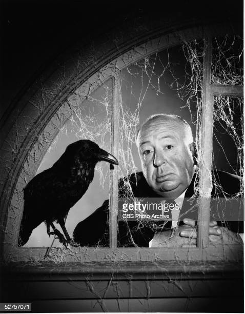 Portrait of Englishborn American film director Alfred Hitchcock as he stands behind a fake window which is covered with fake cobwebs and on the sill...