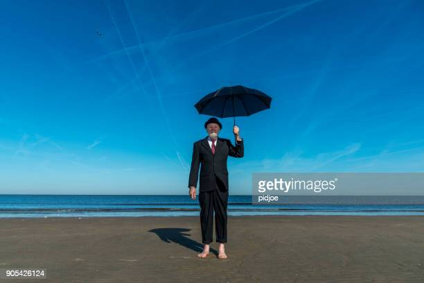 """Portrait of Englishman with bowler hat and umbrella stands barefoot on the beach Looking at the camera.""""nConcept for the Brexit referendum."""