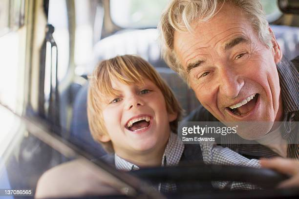 Portrait of enthusiastic grandfather and grandson behind steering wheel