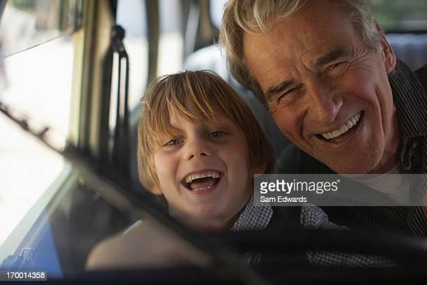 Porträt von begeisterten Großvater und Enkel hinter dem Lenkrad
