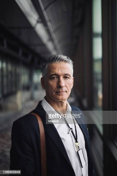 portrait of entrepreneur standing in office corridor - mature men stock pictures, royalty-free photos & images