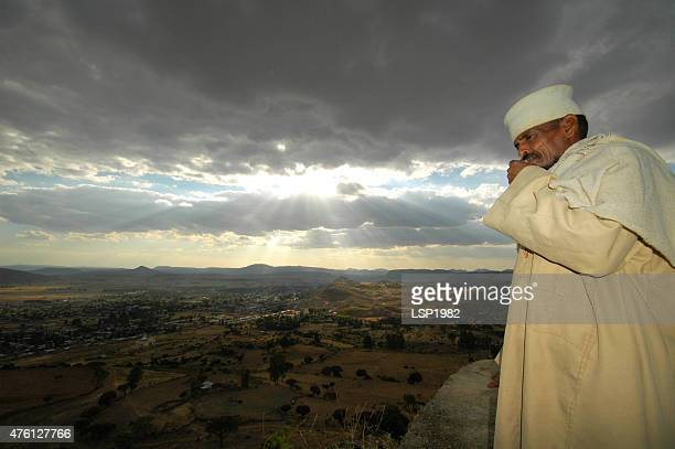 portrait of ethiopian priest standing on top of a mountain. - axum stock photos and pictures