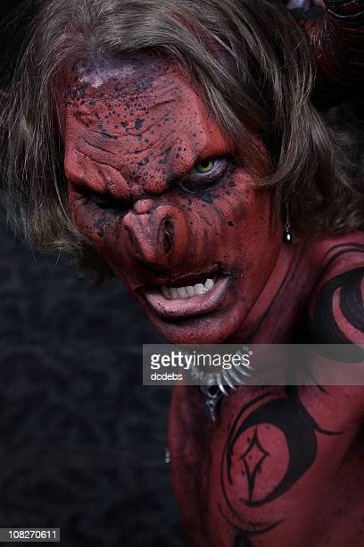 portrait of evil demon in red and black body paint - devil costume stock photos and pictures