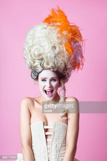 Portrait de femme baroque excitée, portant perruque, fond rose