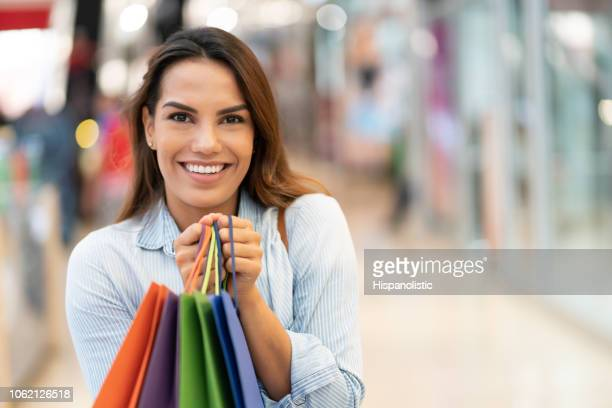 portrait of excited beautiful woman looking at camera smiling while holding her shopping bags - hispanolistic stock photos and pictures