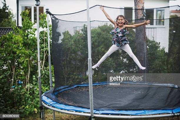 Portrait of excited girl jumping on trampoline at yard