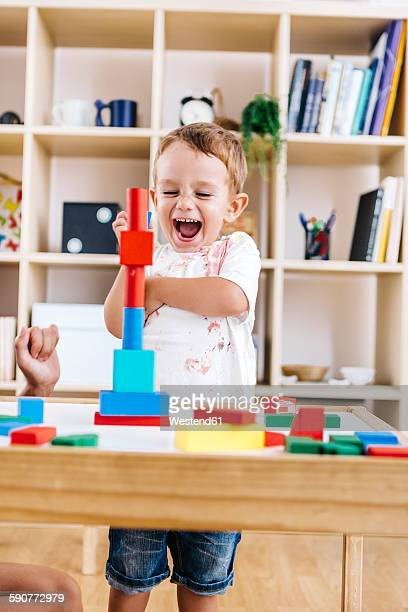Portrait of excited little boy playing with building bricks