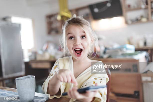 portrait of excited little girl in the kitchen pointing at smartphone - bambine femmine foto e immagini stock