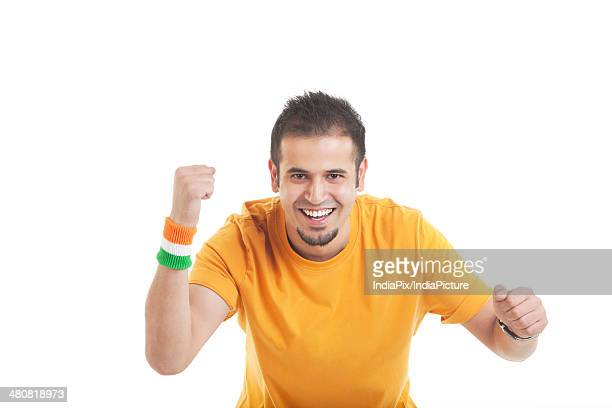 Portrait of excited man cheering over white background
