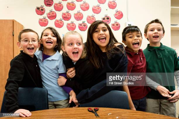 portrait of excited students in classroom - multiculturalism stock pictures, royalty-free photos & images