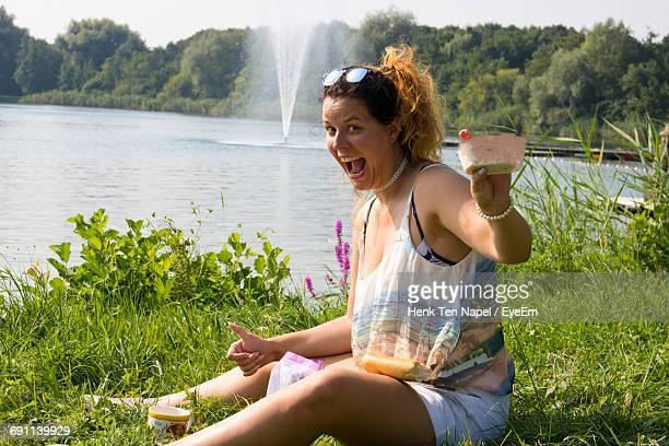 Portrait Of Excited Woman Holding Food While Sitting On Grassy Field By Lake At Park
