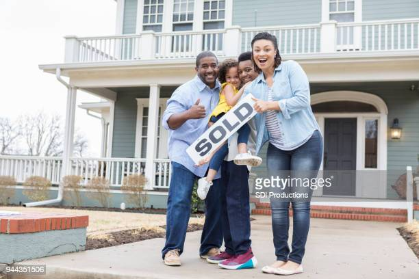 portrait of excited young family in front of new home - selling stock pictures, royalty-free photos & images