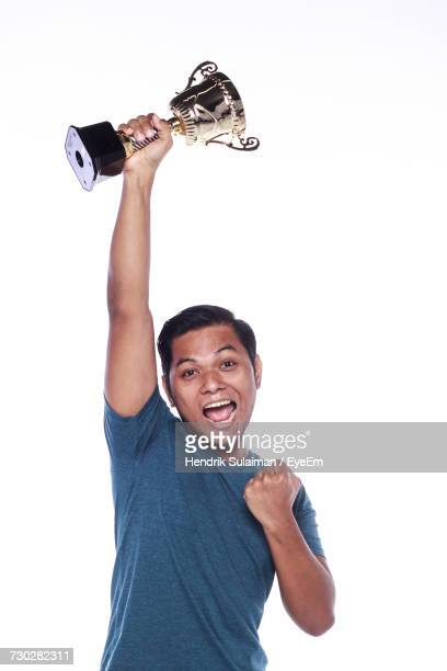 Portrait Of Excited Young Man Holding Trophy Against White Background