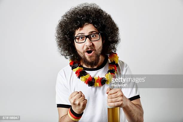 Portrait of excited young man with beer bottle and German football fan articles